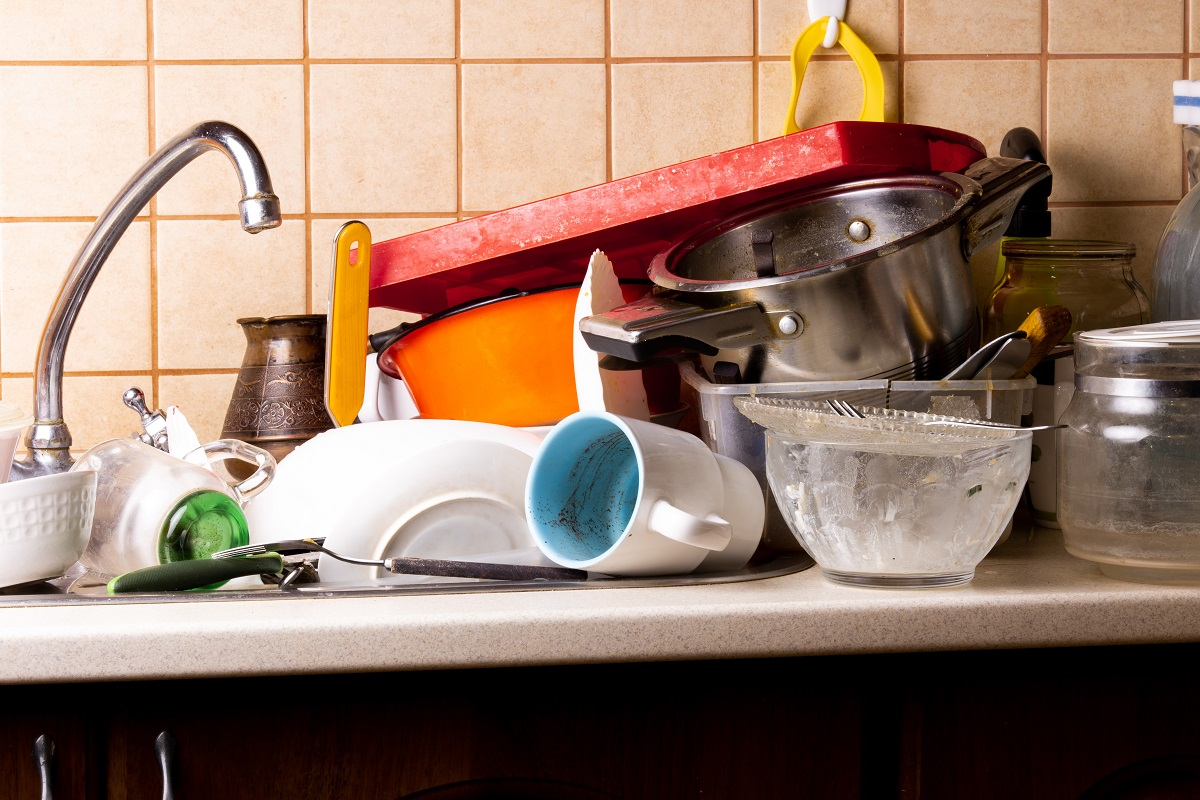A lot of dirty dishes lie in the sink in the kitchen that needs
