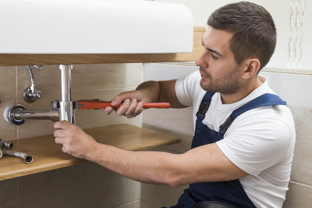 man plumber fixing pipes