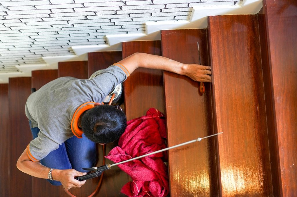 Pest / termites control services on wood stair in the new house that have termites signs inside it.