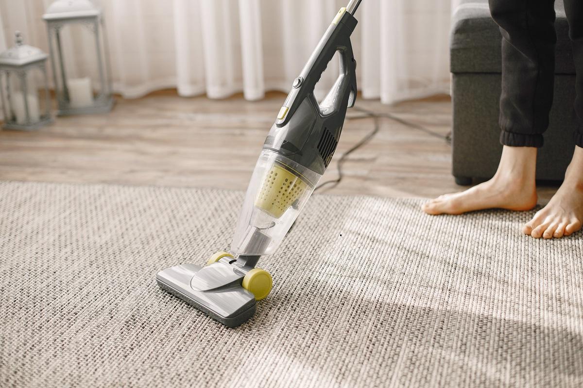 Woman vacuuming mat at home in a good mood